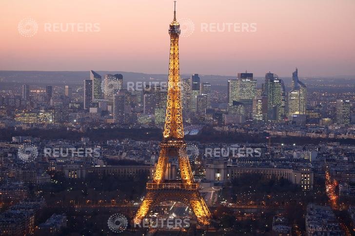 A general view show the illuminated Eiffel Tower and the skyline of La Defense business district (Rear) at night in Paris, France, November 28, 2016. REUTERS/Charles Platiau