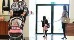 Enquanto uma mulher passeia com o seu cão em um carrinho de bebê, outra passeia com seus filhos na coleira! Será verdade? (foto: Reprodução/Facebook)