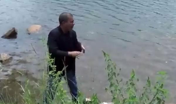 Sujeito às margens de uma das barragens do Sistema Cantareira mostrando que o local tem muita água! (foto: reprodução/Facebook)