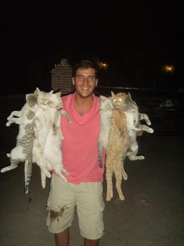 Homem exibe sorridente vários gatos mortos!