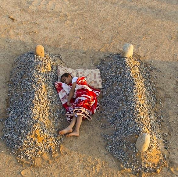 Garoto sírio dorme entre os túmulos de seus pais! Será verdade?