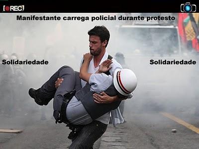 Policial ferido sendo carregado por manifestante