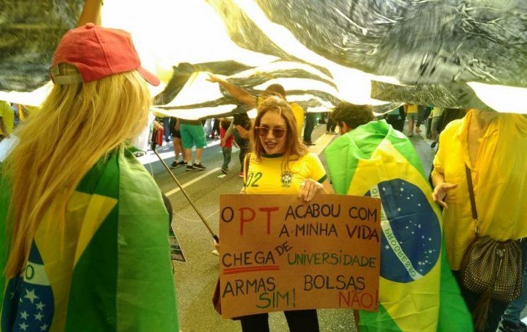 """Conheça a verdade sobre a manifestante com o cartaz: """"Chega de universidade. Armas Sim!"""""""